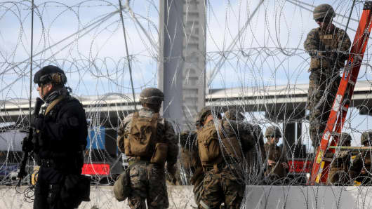 A U.S. Customs and Border Protection (CBP) agent (L) stands watch as U.S. troops set up concertina wire at the San Ysidro port of entry during a 'large-scale operational readiness exercise' which briefly closed the border crossing on November 22, 2018 in Tijuana, Mexico.