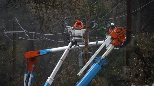 Pacific Gas and Electric (PG&E) crews repair power lines that were destroyed by the Camp Fire on November 21, 2018 in Paradise, California.