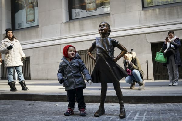 A child stands next to the 'Fearless Girl' after a ceremony to unveil the statue's new location across from the New York Stock Exchange on Dec. 10, 2018 in New York City.