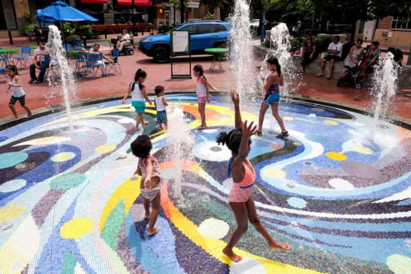 Children frolic in a splash pool in Silver Spring, Md., on July 5, 2018.