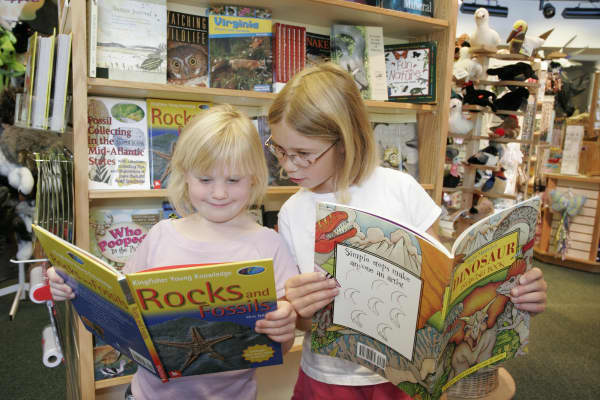 Two girls reading books in the gift shop at Virginia Living Museum.