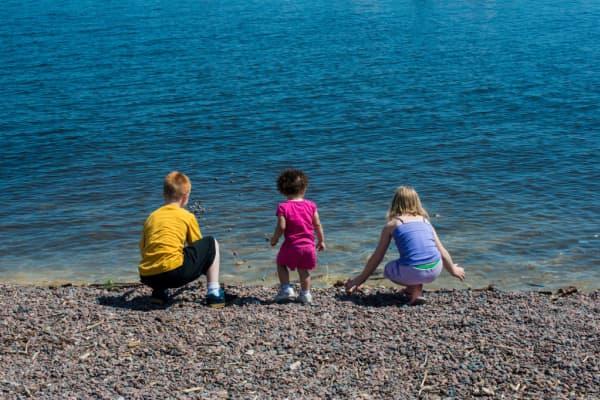 Three siblings skimming rocks into Lake Superior in Duluth, Minn.