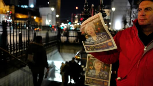 Copies of the Evening Standard, London's daily free newspaper showing Britain's Prime Minister Theresa May are handed out in Westminster in central London on December 12, 2018.