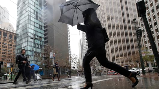 A woman carries an umbrella while crossing a street in San Francisco, Tuesday, Jan. 15, 2019.