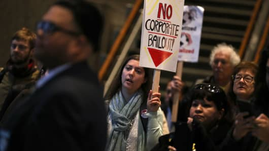 Protesters hold signs as they stage a demonstration inside the lobby of the Pacific Gas and Electric (PG&E) headquarters on December 11, 2018 in San Francisco, California.