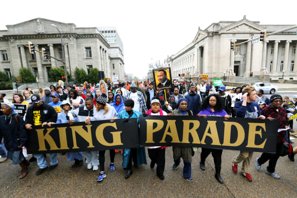 Marchers carry signs through downtown Memphis during the annual Martin Luther King Day march in Memphis, Tenn.