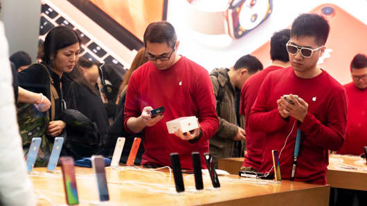 Employees serve customers inside an Apple store in Hong Kong, China, on Thursday, Jan. 3, 2019.