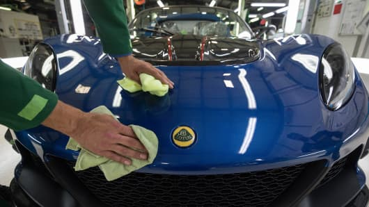An employee polishes a Lotus Exige sports coupe automobile as it moves down the inspection line at the Group Lotus Plc automobile factory in Hethel, U.K., on Thursday, Aug. 10, 2017.