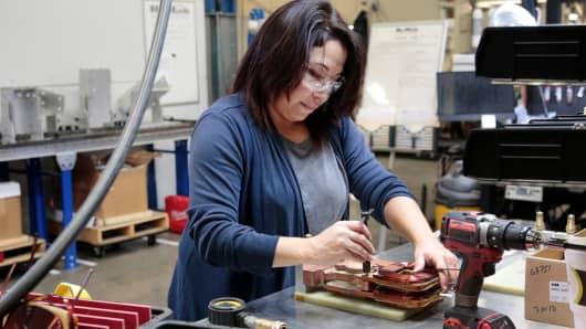 Assembly product worker Donna Gonzalez works on a sub-assembly to a water cooled transformer at RoMan Manufacturing in Grand Rapids, Michigan, December 12, 2018.