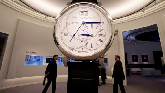 Visitors pass a giant model of a luxury A. Lange & Soehne wristwatch, manufactured by Lange Uhren GmbH, a watchmaking unit of Cie. Financiere Richemont SA.