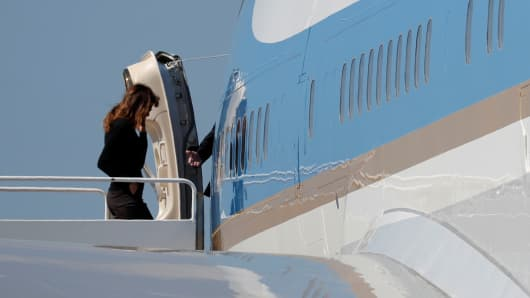 President Donald Trump reaches back for first lady Melania Trump as they board Air Force One upon departure from West Palm Beach, Florida, U.S., March 3, 2018.