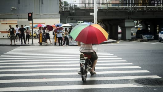 A man holding an umbrella rides a electric bicycle through an intersection as rain falls in Shenzhen, China, on Thursday, June 7, 2018.
