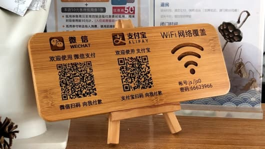 A wooden sign for mobile pay QR codes at a store in Suzhou, China.