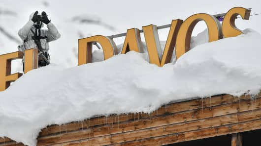 "A policeman wearing camouflage clothing stands on the rooftop of a hotel, next to letters covered in snow reading ""Davos,"" near the Congress Centre ahead of the World Economic Forum (WEF) annual meeting on January 21, 2019 in Davos, Switzerland."