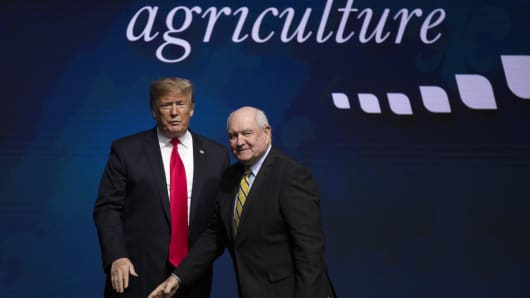 President Donald Trump, left, greets Sonny Perdue, U.S. secretary of agriculture, on stage during the 100th American Farm Bureau Federation Convention in New Orleans, Louisiana, U.S., on Monday, Jan. 14, 2019.