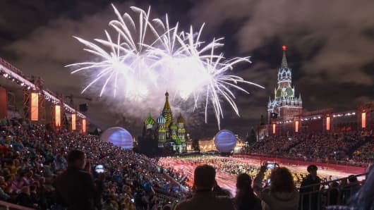People look at fireworks above Saint Basil's Cathedral during the 'Spasskaya Tower' international military and music festival on the Red Square in Moscow on August 26, 2017.