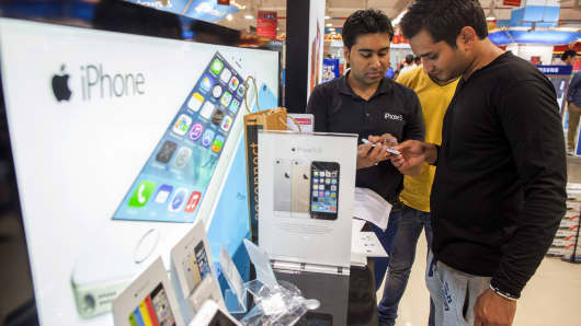 A customer views an Apple Inc. iPhone 5s at a Reliance Digital store, a subsidiary of Reliance Industries Ltd., in New Delhi, India, on Saturday, Nov. 2, 2013. Reliance Communications Ltd. is the first Indian carrier to sell Apples iPhone with a service contract. Reliance will offer customers the iPhone 5S and 5C a two-year contract with bundled data services. Photographer: Prashanth Vishwanathan/Bloomberg via Getty Images