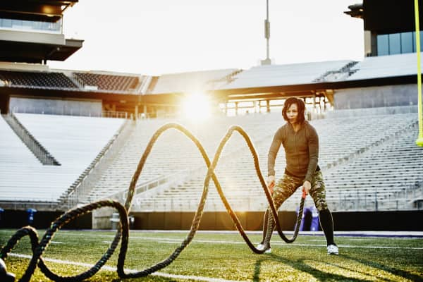 Female athlete working out with battle rope during training session on field in stadium.