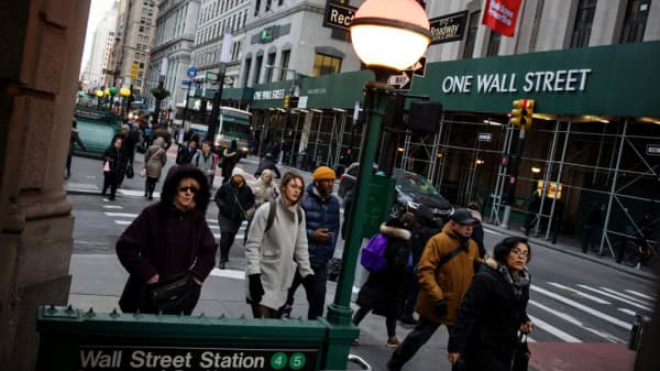 Pedestrians walk along Broadway near the New York Stock Exchange.