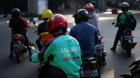 A Go-Jek motorcycle taxi driver travels through traffic in Jakarta, Indonesia, on Saturday, Aug. 4, 2018.