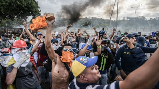 Demonstrators call slogans while barricades see burning in the background during a demonstration against Nicola Maduro's politics. Meetings against the government of Venezuelan President Nicholas Maduro and also to commemorate the 61st anniversary of Markos Perez Jimenez's dictatorship in Caracas
