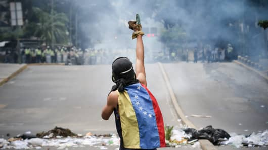 Opposition activists wearing gas masks clash with riot police during an anti-government protest in Caracas.