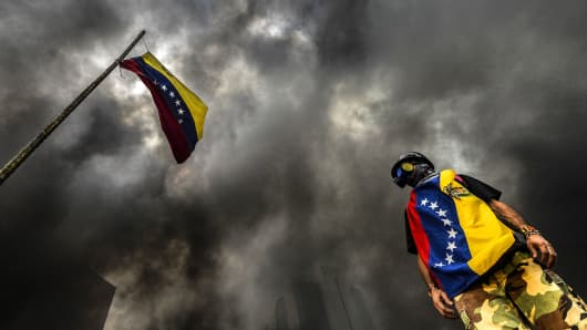An anti-government demonstrator stands next to a national flag during an opposition protest blocking the Francisco Fajardo highway in Caracas on May 27, 2017.