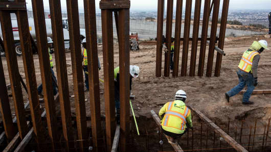 A construction crew works on replacing the US-Mexico border fence as seen from Tijuana, in Baja California state, Mexico, on January 9, 2019.
