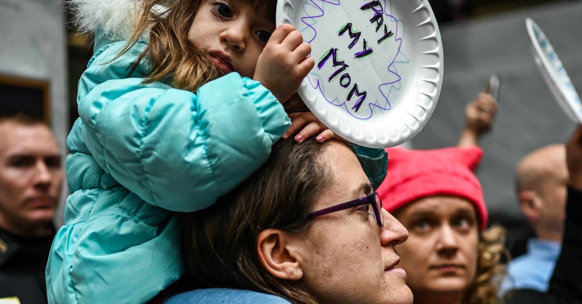 Two-year old Rosa Rivera is carried by her  mother, Tania Alfonso, 38, a federal worker, as Union members, including National Federation of Federal Employees and SEIU, and furloughed federal workers rally in Washington, D.C. on Wednesday, January 23, 2019.