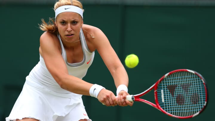 LONDON, ENGLAND - JULY 02:  Sabine Lisicki of Germany plays a backhand during the Ladies' Singles quarter-final match against Kaia Kanepi of Estonia on day eight of the Wimbledon Lawn Tennis Championships at the All England Lawn Tennis and Croquet Club at Wimbledon on July 2, 2013 in London, England.