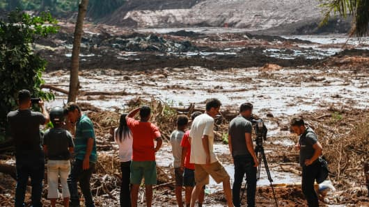 25 January 2019, Brazil, Brumadinho: People observe the mud masses after the break of a dam at the Feijão iron ore mine.