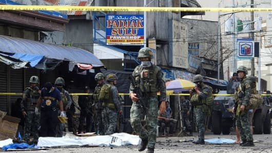 Policemen and soldiers keep watch as body bags (in white), containing the remains of blast victims, as seen in a cordoned area outside a church in Jolo, Sulu province on the southern island of Mindanao, on January 27, 2019. - At least 18 people were killed when two bombs hit a church on a southern Philippine island that is a stronghold of Islamist militants, the military said, days after voters backed the creation of a new Muslim autonomous region.
