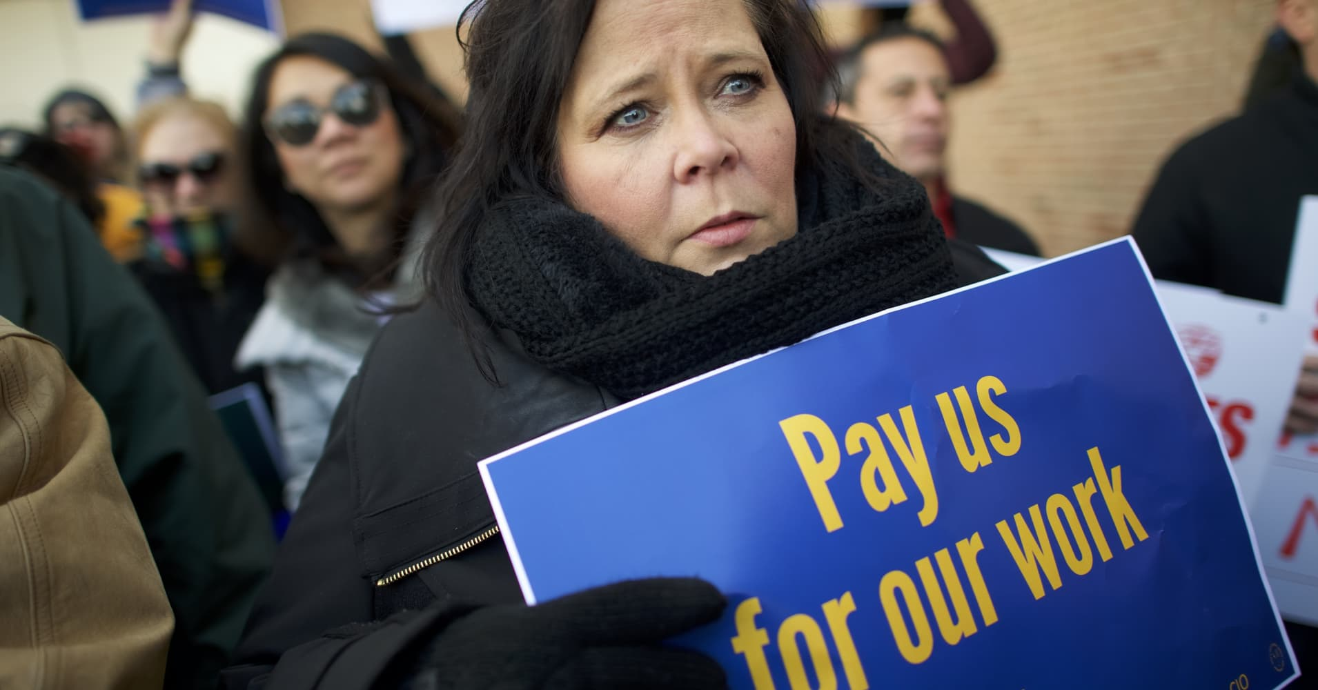 Marie Owens Powell holds a placard stating 'Pay us for our work' while demonstrating with Philadelphia Airport TSA and airport workers outside the Philadelphia International Airport on January 25, 2019 in Philadelphia, Pennsylvania.