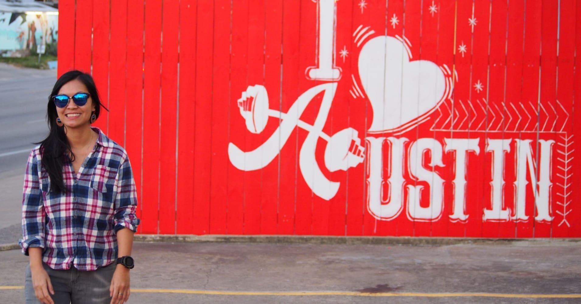 """A woman stands near an """"I love Austin"""" mural in Austin, Texas."""