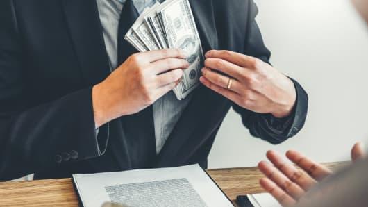 Corruption concept,Business man passing money dollar bills corruption bribery to businessman manager
