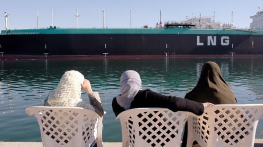 Women observe the Tenaga Satu, a Liquefied Natural Gas (LNG) tanker owned by MISC Berhad, a Malaysian shipping company, as it sails northbound on the Suez Canal in Ismailia, Egypt, on Tuesday, Dec. 11, 2007.
