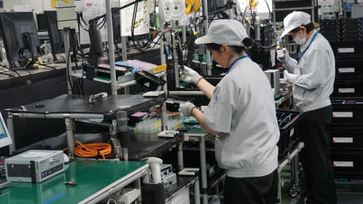 Employees of the Japanese electronics group Panasonic work in a factory building.