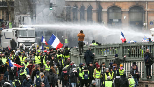 A police vehicle sprays water cannon at protesters during an anti-government demonstration in Paris on January 26, 2019.
