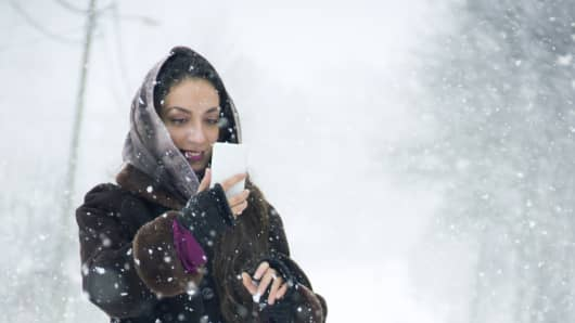 Woman using her phone in the snow.