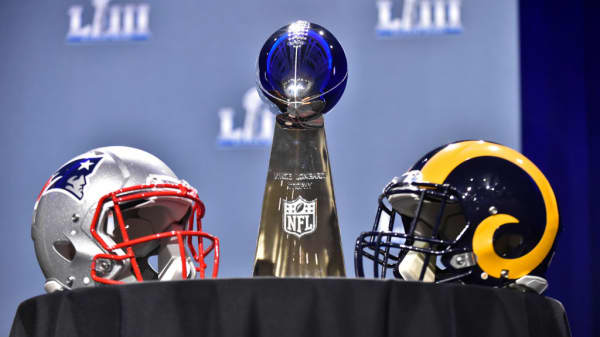 The Vince Lombardi Trophy sits on a table between the New England Patriots and Los Angeles Rams helmets at the Georgia World Congress Center on January 30, 2019, in Atlanta, GA
