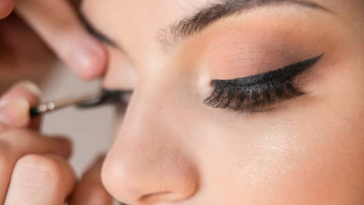 Detail of caucasian model false eyelashes during make-up session. The make-up artist is applying a black eyeliner with the brush