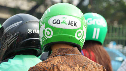Bike passengers wearing Helmet with Gojek logo.