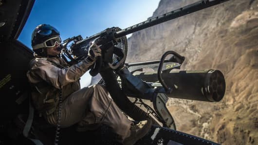 A Marine Corps Huey door gunner with unloads on a target at the Chocolate Mountain Aerial Gunnery Range, Calif., Oct. 2, 2013.