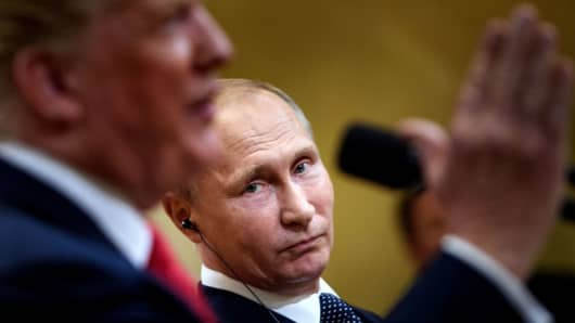 Russia's President Vladimir Putin listens while U.S. President Donald Trump speaks during a press conference in Helsinki, Finland.