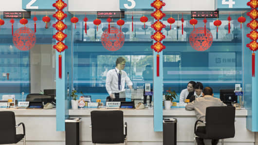 Employees work behind a counter inside a Bank of Taizhou Co. branch at the company's headquarters in Taizhou, China, on Tuesday, Nov. 7, 2017.