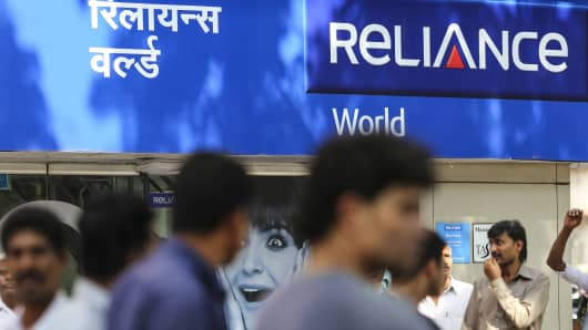 Pedestrians walk past a Reliance Communications retail store in Mumbai, India.