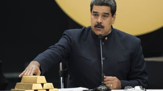 Nicolas Maduro, Venezuela's president, speaks as he touches a stack of 12 Kilogram gold ingots during a news conference on the country's cryptocurrency, known as the Petro, in Caracas, Venezuela, on Thursday, March 22, 2018.