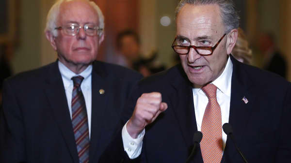 Senate Minority Leader Charles Schumer (D-NY) (R) is flanked by Sen. Bernie Sanders on Capitol Hill.