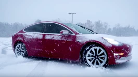 A Tesla Model 3 in the snow.