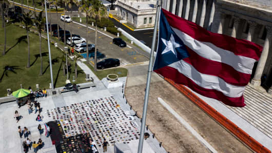 A Puerto Rican flag flies above empty pairs of shoes outside the Capitol building in this aerial photograph taken during a protest against the government's reporting of the death toll from  Hurricane Maria in San Juan, Puerto Rico, on Friday, June 1, 2018.